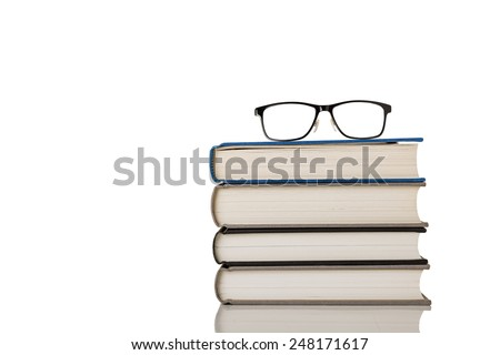 A Pair of Glasses on Stack of Books Isolated on a White Background.  - stock photo