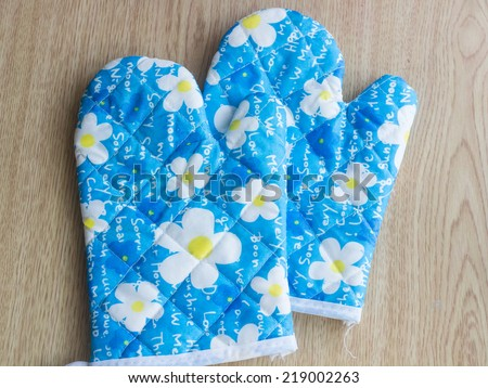 A pair of glove for carry hot thing when finish cooking from a microwave, isolated on wood - stock photo