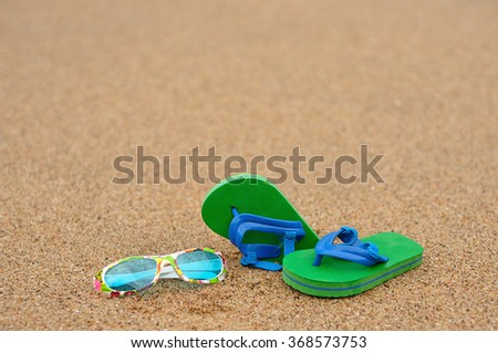 A pair of green and blue flip flops with colorful sunglasses on the beach - stock photo