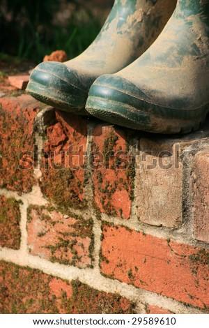 A pair of green muddy wellington/garden boots set atop a red bricked garden wall. - stock photo