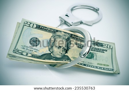 a pair of handcuffs and some dollar bills depicting the idea of arrest for bribery or corruption - stock photo
