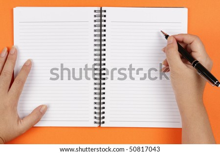 A pair of hands, a pen and a notebook on an orange background - stock photo