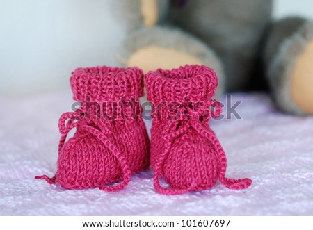 A pair of knitted, bright pink baby booties - stock photo