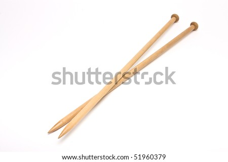 A pair of large wooden knitting needles from low perspective isolated against white background. - stock photo