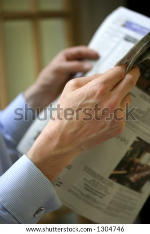 A pair of man's hands clutching on to a newspaper. Concept : Keeping up with the world. Very shallow DoF. - stock photo