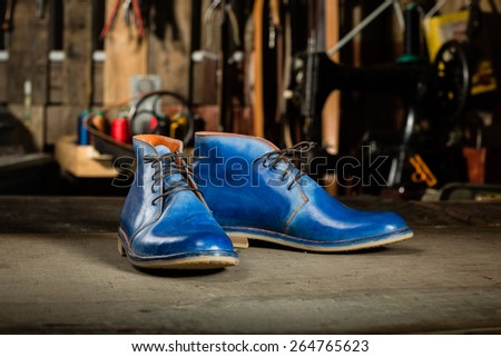 A pair of men's leather shoes in the shoemaker's workshop on working desk. - stock photo