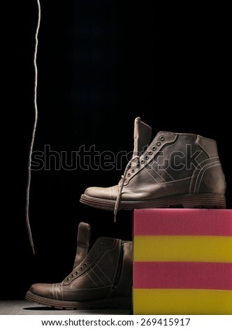 A Pair Of Men's Winter Boots on dark backgrounds with sponge - stock photo