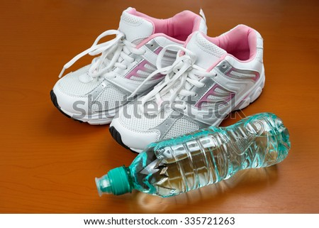 A pair of new girl sport indoor shoes and bottle of water on wooden surface - stock photo