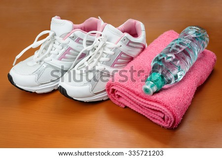A pair of new girl sport indoor shoes with towel and bottle of water at wooden surface as concept of healthy lifestyle - stock photo