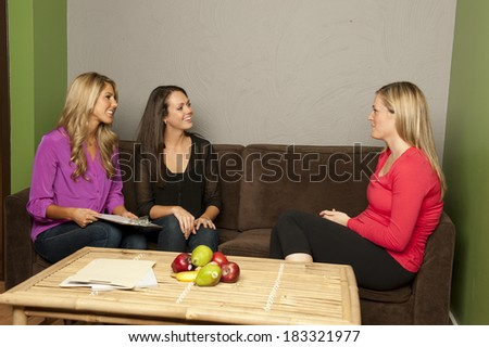 A pair of nutritionist consult a pregnant female on a couch. - stock photo