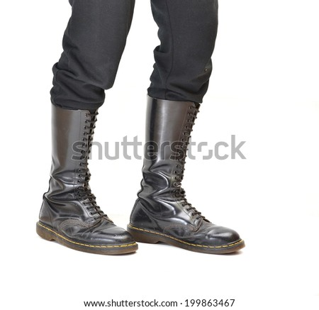 A pair of old and rugged man's/unisex knee-high black 20-eyelet lace-up combat boots - stock photo