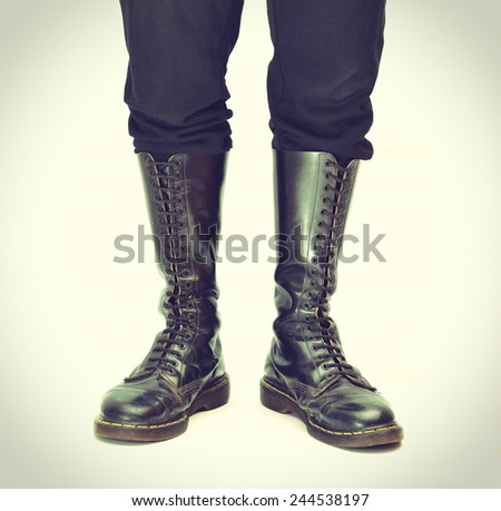 A pair of old and rugged men's/unisex knee-high black 20-eyelet lace-up combat boots - vintage processes - stock photo