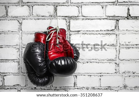 A pair of old boxing gloves hanging against a white brick wall. - stock photo