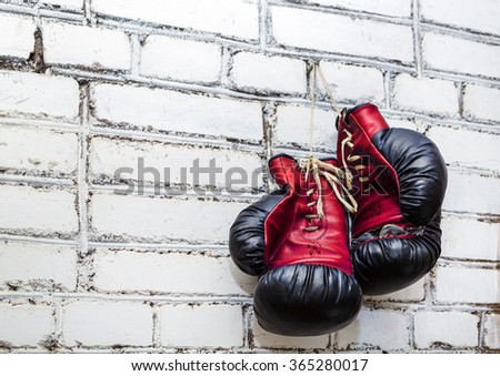 A pair of old boxing gloves hanging on white brick wall background. - stock photo
