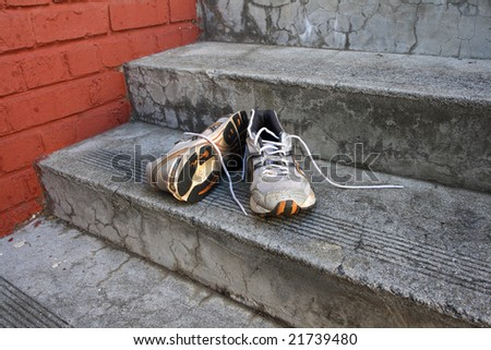 A pair of old running shoes on cement steps with a red brick wall as a background. - stock photo