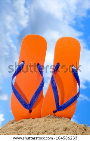 a pair of orange flip-flops on the sand over the blue sky - stock photo