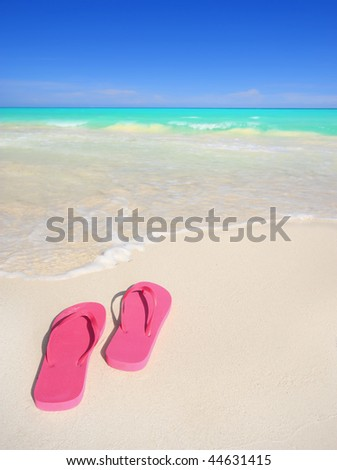 A pair of pink flip-flop sandals on a stunning white sand tropical beach. Travel & vacation concepts. - stock photo