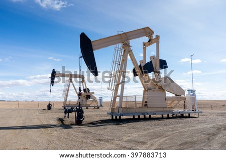 A pair of pumpjacks extracting oil out of an overground well in rural Alberta, Canada. These jacks can extract between 5 to 40 litres of crude oil and water emulsioin at each stroke. - stock photo