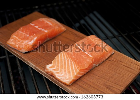 A pair of raw wild Alaskan Salmon fillets on a cedar plank being grilled. - stock photo
