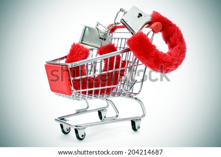 a pair of red sexy fluffy handcuffs in a shopping cart depicting the idea of paying for sex or the sex industry or the sex commerce - stock photo