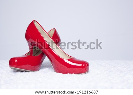 A pair of sexy, red patent leather pumps sit atop a white fur surface with a white background - stock photo