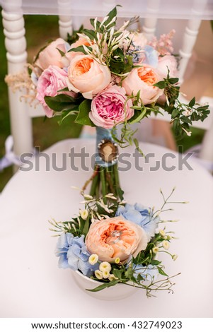 a pair of simple silver wedding rings on a flower bouquet - stock photo