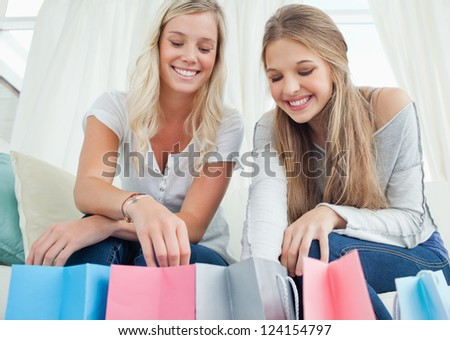 A pair of smiling girls looking inot the bags by their feet - stock photo