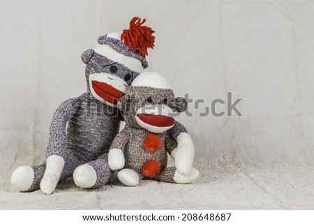 A pair of sock monkeys sitting next to each other on a table. - stock photo