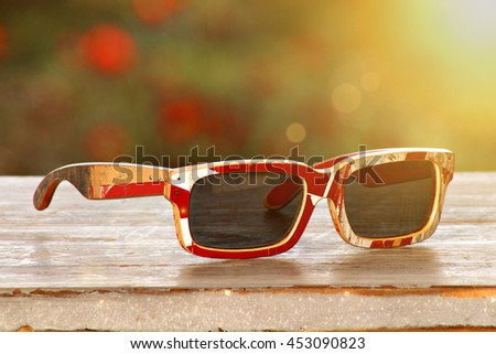 A pair of sunglasses, made out of a recycled skateboard deck. Added lens flare. - stock photo