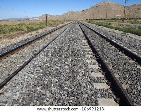 A pair of train tracks curve in the distance. - stock photo