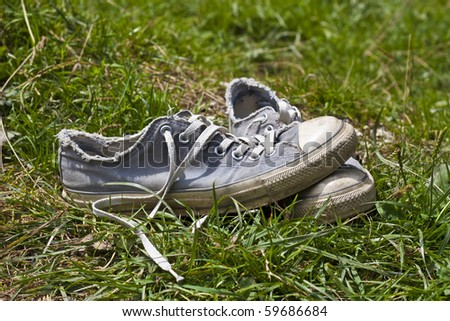 A pair of used grey sport shoes in meadow - stock photo