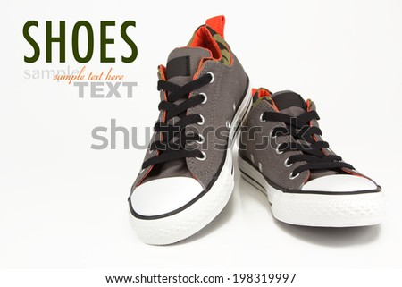 A pair of vintage grey canvas sneakers with camouflage trim and black laces. Shoes shot in studio on a white background with sample text.  - stock photo