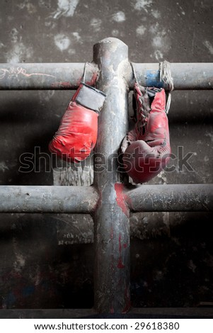 A pair of well used, dusty Muay Thai boxing gloves hanging against a grungy boxing ring - stock photo
