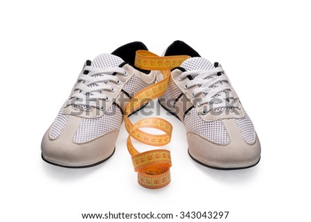 A pair of white sports shoes with measurement tape on white background - stock photo