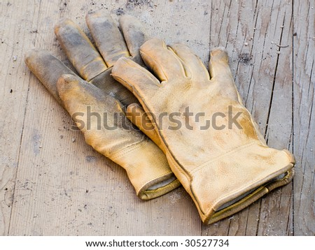 A pair of work gloves lying on planks of wood - stock photo