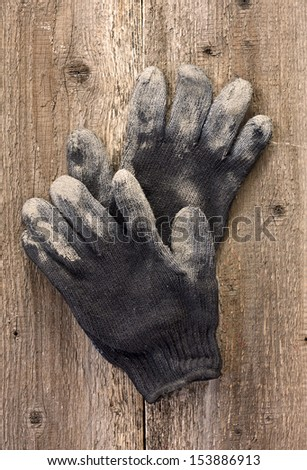 A pair of work gloves on the old wooden background - stock photo