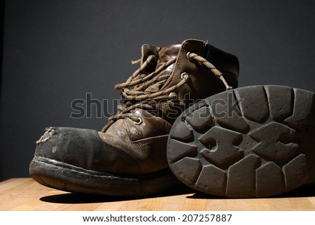 A pair of worn work boots showing their texture.            - stock photo