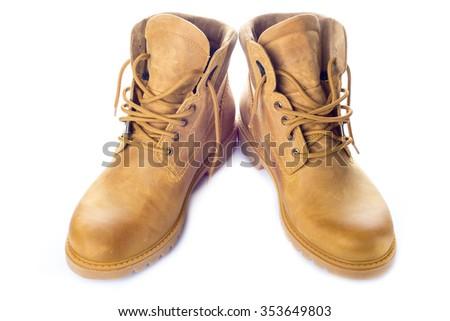 A pair of yellow leather boots isolated on a white background - stock photo
