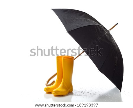 A pair of yellow rainboots and a black umbrella on a white background with copy space - stock photo