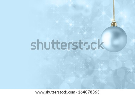 A pale blue Christmas bauble, suspended on gold string against a star filled twinkly bokeh background, fading into solid colour to provide copy space on the left side. - stock photo