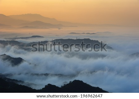 A pale orange sunset seen from high above the clouds. - stock photo