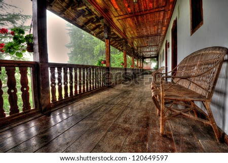 A pale teak wood garden bench on a stone terrace before a background of fall foliage. - stock photo