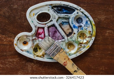 A palette of aquarelle paints with a brush on the wooden background - stock photo