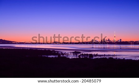 A Panorama of Auckland City, Harbour Bridge and Rangitoto Island at Sunrise - stock photo