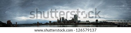 A panorama of Cincinnati Ohio under a cloudy sky. - stock photo
