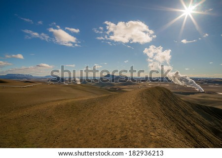 A panoramic icelandic landscape in the Krafla region with a steam volcano in the background at afternoon sun - stock photo