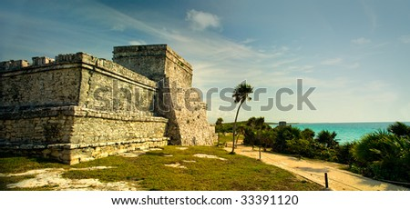 A panoramic image of the main temple structure in the ancient Mayan city at Tulum, Mexico. - stock photo