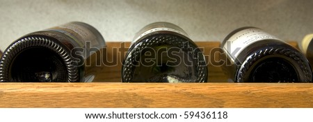 A panoramic image of wine bottles on a shelf. - stock photo