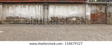 A panoramic stretch of old masonry wall along a cobble stone sidewalk. - stock photo