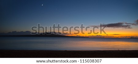 A panoramic view of a new day as the sun rises behind Rangitoto Island, Auckland, New Zealand - stock photo